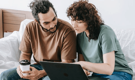 Two people looking at a website on a laptop